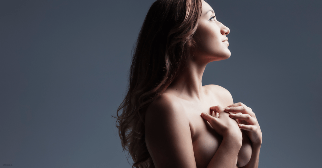 A woman thinks about her breast augmentation options in 2019.